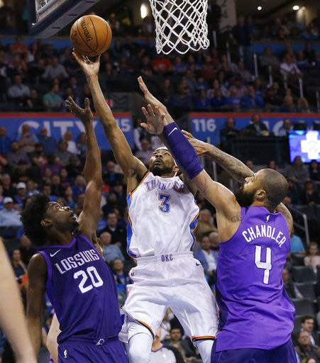 Oklahoma City Thunder forward Corey Brewer (3) shoots between Phoenix Suns guard Josh Jackson (20) and center Tyson Chandler (4) during the first half of an NBA basketball game in Oklahoma City, Thursday, March 8, 2018.