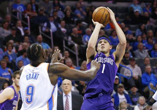 Phoenix Suns guard Devin Booker (1) shoots over Oklahoma City Thunder forward Jerami Grant (9) during the second half of an NBA basketball game in Oklahoma City, Thursday, March 8, 2018.