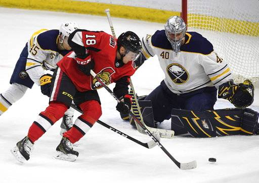 Ottawa Senators' Ryan Dzingel (18) makes his way past Buffalo Sabres' Brendan Guhle (45) as goaltender Robin Lehner (40) eyes the puck during second period NHL hockey action in Ottawa, Thursday, March 8, 2018. (Justin Tang/The Canadian Press via AP)