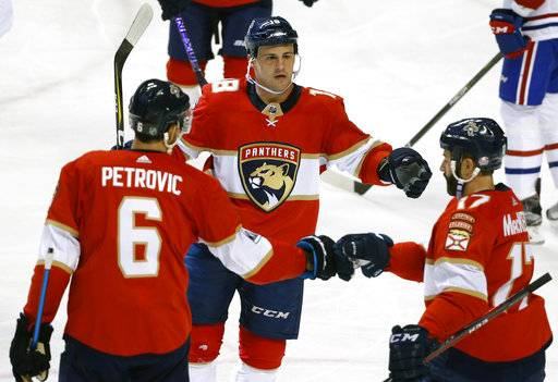 Florida Panthers center Micheal Haley, center, celebrates with defenseman Alexander Petrovic (6) and center Derek MacKenzie (17) after scoring during the second period of an NHL hockey game against the Montreal Canadiens, Thursday, March 8, 2018 in Sunrise, Fla.