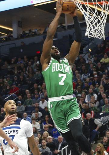 Boston Celtics's Jaylen Brown lays up as Minnesota Timberwolves' Taj Gibson, left, looks on in the first half of an NBA basketball game Thursday, March 8, 2018, in St. Paul, Minn.
