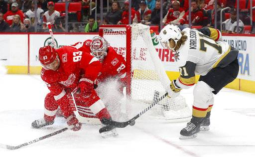 Detroit Red Wings defenseman Trevor Daley (83) deflects a shot by Vegas Golden Knights center William Karlsson (71) in front of goaltender Jimmy Howard during the first period of an NHL hockey game Thursday, March 8, 2018, in Detroit.