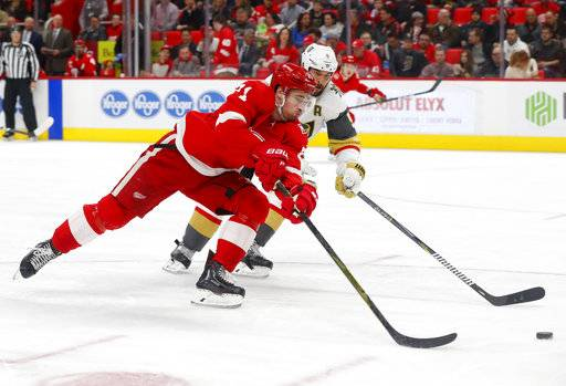 Detroit Red Wings center Dylan Larkin (71) shoots on Vegas Golden Knights defenseman Deryk Engelland (5) during the second period of an NHL hockey game Thursday, March 8, 2018, in Detroit.
