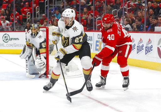 Detroit Red Wings center Henrik Zetterberg (40) lifts the puck from Vegas Golden Knights defenseman Shea Theodore (27) during the second period of an NHL hockey game Thursday, March 8, 2018, in Detroit.