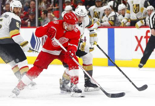 Detroit Red Wings left wing Justin Abdelkader (8) takes the puck from Vegas Golden Knights center Jonathan Marchessault (81) during the first period of an NHL hockey game Thursday, March 8, 2018, in Detroit.