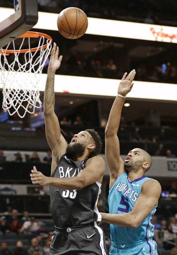Brooklyn Nets' Allen Crabbe (33) shoots past Charlotte Hornets' Nicolas Batum (5) during the first half of an NBA basketball game in Charlotte, N.C., Thursday, March 8, 2018.