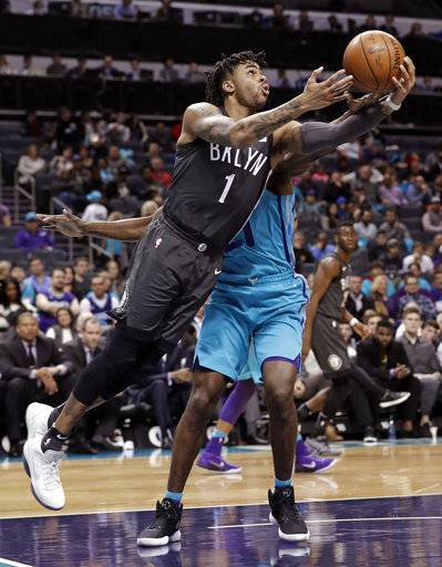 Brooklyn Nets' D'Angelo Russell (1) drives past Charlotte Hornets' Treveon Graham (21) during the first half of an NBA basketball game in Charlotte, N.C., Thursday, March 8, 2018.