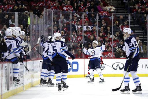Winnipeg Jets players celebrate a goal by Joel Armia (40), of Finland, during the second period of an NHL hockey game against the New Jersey Devils, Thursday, March 8, 2018, in Newark, N.J.