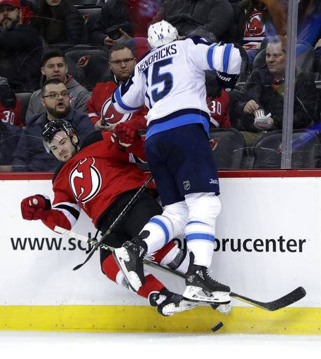 New Jersey Devils defenseman Will Butcher, left, is checked by Winnipeg Jets center Matt Hendricks during the second period of an NHL hockey game, Thursday, March 8, 2018, in Newark, N.J.