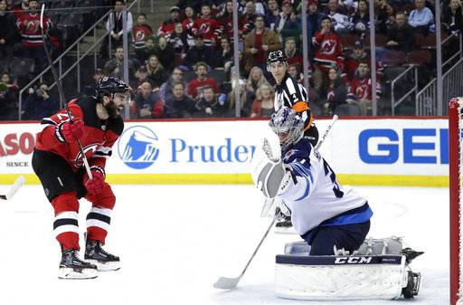 New Jersey Devils right wing Kyle Palmieri, left, reacts after scoring a goal on Winnipeg Jets goaltender Connor Hellebuyck during the second period of an NHL hockey game, Thursday, March 8, 2018, in Newark, N.J.