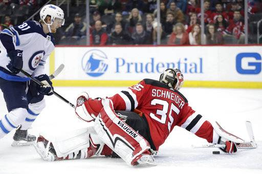 New Jersey Devils goaltender Cory Schneider (35) dives to deflect the puck out of his crease as Winnipeg Jets left wing Kyle Connor (81) attacks during the first period of an NHL hockey game, Thursday, March 8, 2018, in Newark, N.J.
