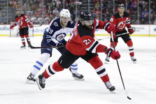 New Jersey Devils right wing Kyle Palmieri (21) shoots with Winnipeg Jets right wing Patrik Laine (29), of Finland, in tow during the second period of an NHL hockey game, Thursday, March 8, 2018, in Newark, N.J.