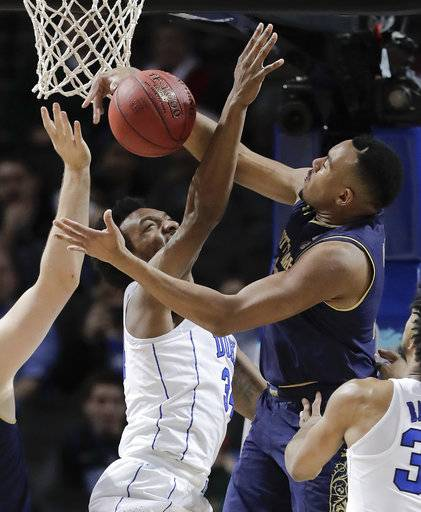 Duke forward Wendell Carter Jr (34) and Notre Dame forward Bonzie Colson (35) battle for a rebound during the first half of an NCAA college basketball game in the Atlantic Coast Conference men's tournament Thursday, March 8, 2018, in New York.
