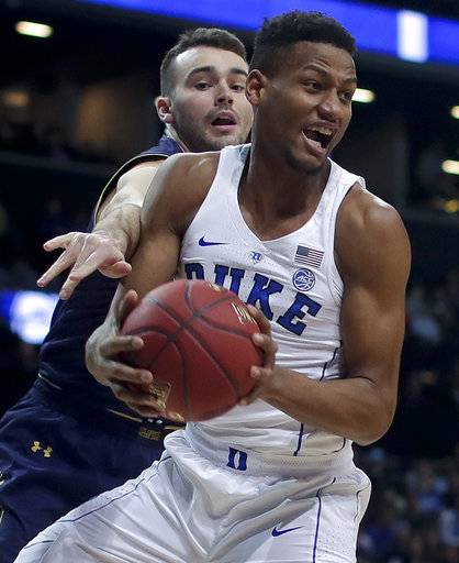 Duke forward Javin DeLaurier (12) pulls down a rebound against Notre Dame forward John Mooney (33) during the first half of an NCAA college basketball game in the Atlantic Coast Conference men's tournament Thursday, March 8, 2018, in New York.