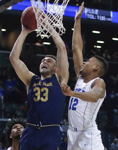 Notre Dame forward John Mooney (33) shoots against Duke forward Javin DeLaurier (12) during the first half of an NCAA college basketball game in the Atlantic Coast Conference men's tournament Thursday, March 8, 2018, in New York.