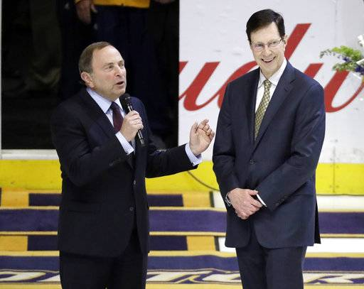 Nashville Predators general manager David Poile, right, is honored by NHL commissioner Gary Bettman before an NHL hockey game between the Predators and the Anaheim Ducks Thursday, March 8, 2018, in Nashville, Tenn. Poile was honored for becoming the winningest general manager in NHL history, a feat he accomplished on March 1 in Edmonton with his 1,320th career victory.