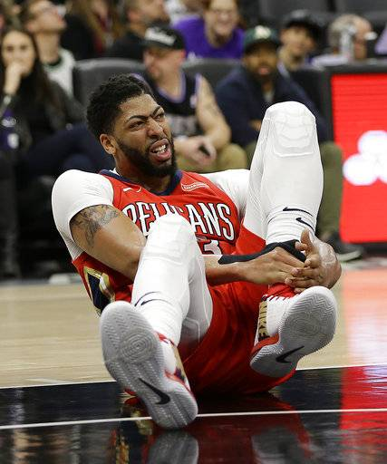 New Orleans Pelicans forward Anthony Davis grabs his ankle after going down during the second half of an NBA basketball game against the Sacramento Kings, Wednesday, March 7, 2018, in Sacramento, Calif. Davis left the court and didn't return to the game as the Pelicans went on to win 114-101.