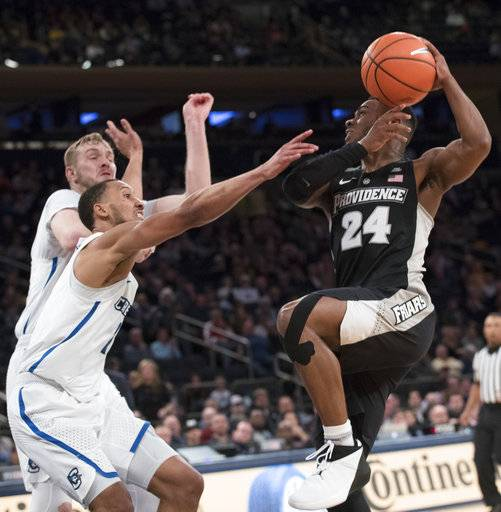 Creighton forward Toby Hegner, left, and guard Davion Mintz, center, pressure Providence guard Kyron Cartwright (24) during the second half of an NCAA college basketball game in the quarterfinals of the Big East conference tournament, Thursday, March 8, 2018, at Madison Square Garden in New York.