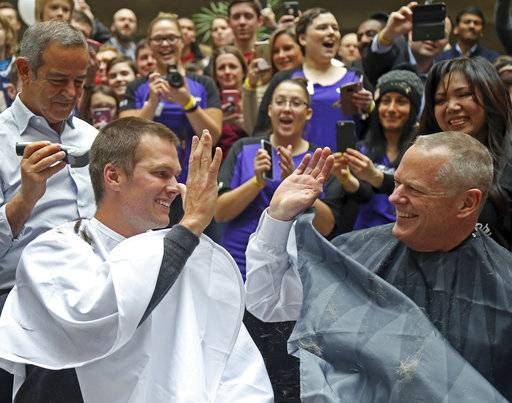 "Massachusetts Gov. Charlie Baker, right, and New England Patriots quarterback Tom Brady, left, high five as they get their heads shaved at the ""Saving By Shaving"" event in support of the Dana-Farber Cancer Institute at Granite Telecommunications in Quincy, Mass., Thursday, March 8, 2018. Brady was the mystery guest at Thursday's ""Saving by Shaving"" annual fundraiser for the Dana-Farber Cancer Institute in Boston. ( John Wilcox /The Boston Herald via AP)"