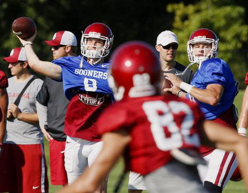 FILE - In this Aug. 17, 2017, file photo, Oklahoma quarterbacks Tanner Schafer, left, and Austin Kendall, right, throw during NCAA college football practice in Norman, Okla. Oklahoma will start figuring out who will replace Heisman Trophy-winning quarterback Baker Mayfield when spring practice opens. The top two contenders will be last year's backup, redshirt junior Kyler Murray, and redshirt sophomore Austin Kendall. Redshirt sophomore Tanner Schafer will get a look, too.