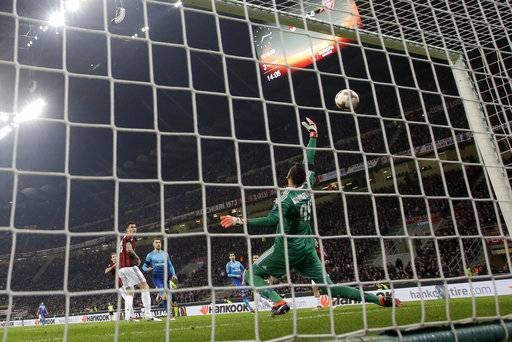 Arsenal's Henrikh Mkhitaryan scores his side's opening goal during the Europa League round of 16 first-leg soccer match between AC Milan and Arsenal, at the Milan San Siro Stadium, Italy, Thursday, March 8, 2018.