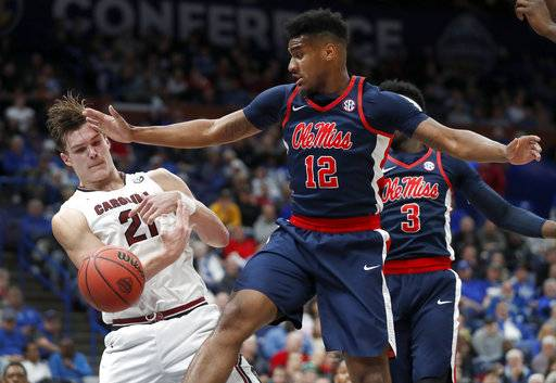 South Carolina's Maik Kotsar (21) tries to keep a ball in bounds as Mississippi 's Bruce Stevens (12) watches during the first half in an NCAA college basketball game at the Southeastern Conference tournament Wednesday, March 7, 2018, in St. Louis.