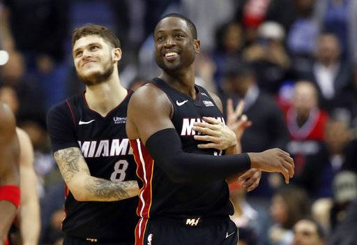 Miami Heat guard Tyler Johnson, left, reacts with guard Dwyane Wade during the overtime period an NBA basketball game against the Washington Wizards, Tuesday, March 6, 2018, in Washington. The Wizards won 117-113.