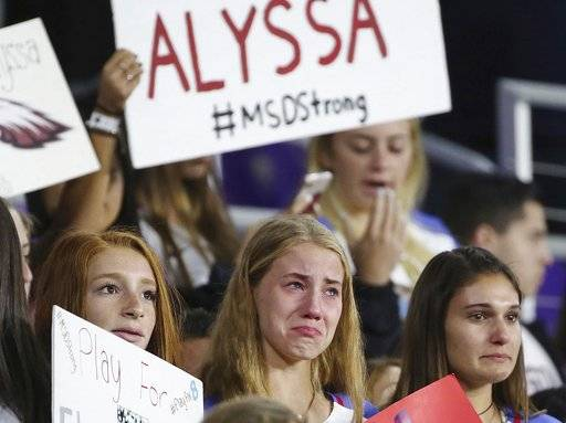 Before the start of the She Believes Cup women's soccer match of USA vs. England at Orlando City Stadium on Wednesday, March 7, 2018,  soccer players and other students from Marjory Stoneman Douglas High School hold signs and weep for their former teammate, Alyssa Alhadeff,  who was killed in the massacre at the South Florida High School on February 14, 2018.   (Stephen M. Dowell/Orlando Sentinel via AP)