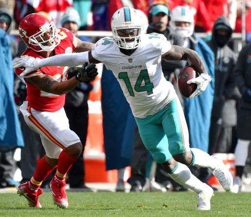 FILE - In this Dec. 24, 2017, file photo, Miami Dolphins wide receiver Jarvis Landry (14) runs away from Kansas City Chiefs defensive back Steven Nelson (20) during the first half of an NFL football game, in Kansas City, Mo. A person familiar with the situation says Miami Dolphins receiver Jarvis Landry has signed his $16 million, one-year franchise tag, easing the path to a potential trade. The person confirmed the signing to The Associated Press on condition of anonymity Thursday, March 8, 2018,  because the Dolphins hadn't announced the move.