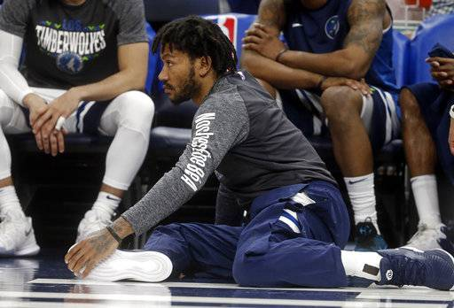 Newly signed Minnesota Timberwolves' Derrick Rose watches his new team in the second half of an NBA basketball game against the Boston Celtics Thursday, March 8, 2018, in St. Paul, Minn. The Celtics won 117-109.