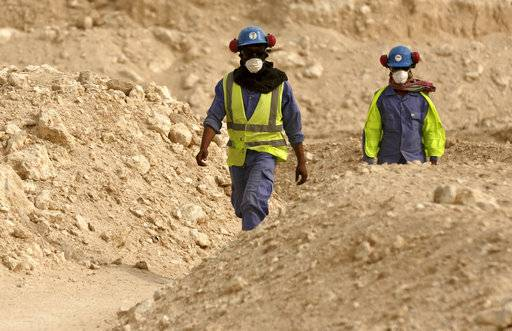 FILE - In this file photo taken during a government organized media tour, workers walk back to the Al-Wakra Stadium worksite being built for the 2022 World Cup, in Doha, Qatar. Qatar World Cup monitors have found workers going more than four months without rest on building sites.