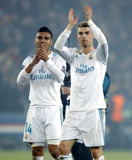 Real Madrid's scorers Casemiro, left, and Cristiano Ronaldo wave to their fans after the round of 16, 2nd leg Champions League soccer match between Paris Saint-Germain and Real Madrid at the Parc des Princes Stadium in Paris, Tuesday, March 6, 2018. Real Madrid won 2-1.