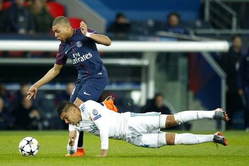 Real Madrid's Casemiro, bottom, tries to stop PSG's Kylian Mbappe during the round of 16, 2nd leg Champions League soccer match between Paris Saint-Germain and Real Madrid at the Parc des Princes Stadium in Paris, Tuesday, March 6, 2018.