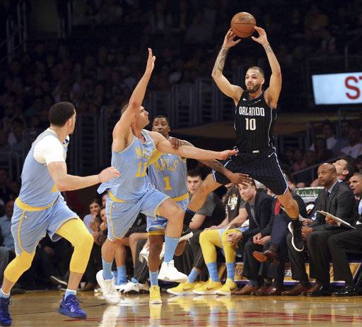 Orlando Magic's Evan Fournier (10) passes the ball over Los Angeles Lakers, including center Brook Lopez (11), during the first half of an NBA basketball game in Los Angeles on Wednesday, March 7, 2018.