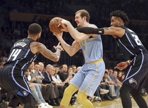 Los Angeles Lakers guard Alex Caruso (4) is defended by Orlando Magic guard Brandon Ingram (14) and forward Wes Iwundu (25), who fouls Caruso during the first half of an NBA basketball game in Los Angeles on Wednesday, March 7, 2018.