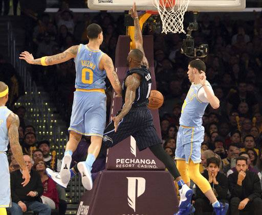 Orlando Magic forward Jonathon Simmons (17) loses the ball as he shoots as Los Angeles Lakers forward Kyle Kuzma (0) and guard Lonzo Ball (2) defend during the second half of an NBA basketball game in Los Angeles Wednesday, March 7, 2018. The Lakers won 108-107.