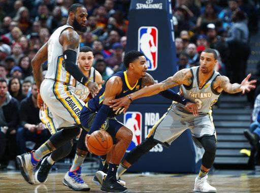 Denver Nuggets guard Gary Harris, center, drives between Cleveland Cavaliers forward LeBron James, left, and guard George Hill during the first half of an NBA basketball game Wednesday, March 7, 2018, in Denver.