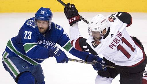Vancouver Canucks defenseman Alexander Edler (23) fights for control of the puck with Arizona Coyotes left wing Brendan Perlini (11) during the second period of an NHL hockey game Wednesday, March 7, 2018, in Vancouver, British Columbia. (Jonathan Hayward/The Canadian Press via AP)