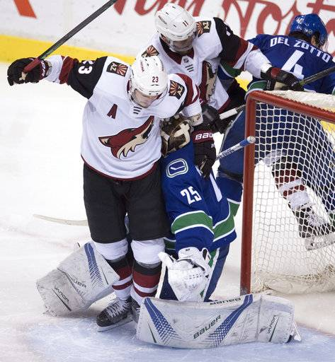 Arizona Coyotes defenseman Oliver Ekman-Larsson (23) and left winger Brendan Perlini (11) crowd Vancouver Canucks goaltender Jacob Markstrom (25) during the third period of an NHL hockey game Wednesday, March 7, 2018, in Vancouver, British Columbia. (Jonathan Hayward/The Canadian Press via AP)