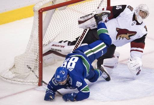 Vancouver Canucks center Sam Gagner (89) flies over Arizona Coyotes goaltender Darcy Kuemper during the third period of an NHL hockey game Wednesday, March 7, 2018, in Vancouver, British Columbia. (Jonathan Hayward/The Canadian Press via AP)