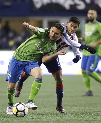 Seattle Sounders midfielder Cristian Roldan, left, is challenged by Guadalajara midfielder Orbelin Pineda during the first half of a CONCACAF Champions League soccer match Wednesday, March 7, 2018, in Seattle.