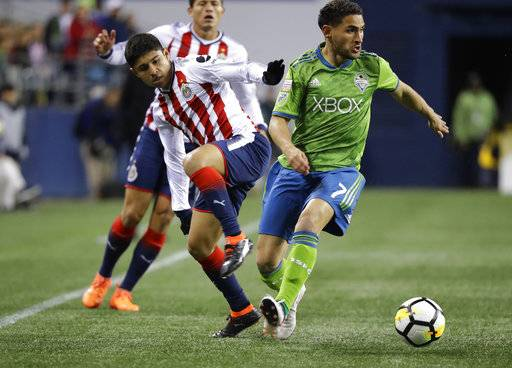Seattle Sounders midfielder Cristian Roldan, right, looks to pass the ball away from Guadalajara midfielder Javier Lopez, center, during the first half of a CONCACAF Champions League soccer match Wednesday, March 7, 2018, in Seattle.