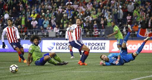 Guadalajara's Alan Pulido, Seattle Sounders' Roman Torres, Guadalajara's Jose Godinez, and Sounders goalkeeper Stefan Frei, from left, watch the ball after Frei deflected a shot during the first half of a CONCACAF Champions League soccer match, Wednesday, March 7, 2018, in Seattle.