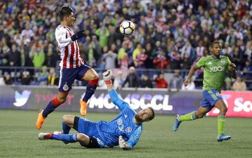 Seattle Sounders goalkeeper Stefan Frei, lower left, watches as Guadalajara forward Alan Pulido, left, jumps over him after Frei deflected a close-range shot by Pulido during the first half of a CONCACAF Champions League soccer match Wednesday, March 7, 2018, in Seattle.