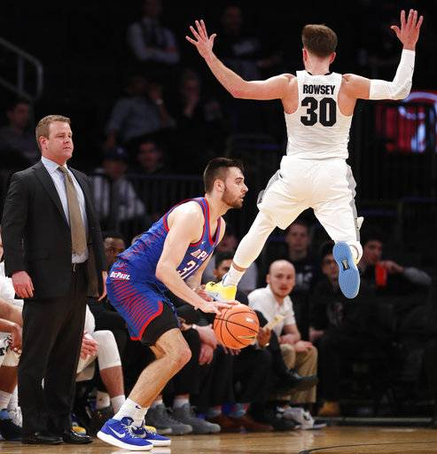 Marquette head coach Steve Wojciechowski, left, watches, as Marquette guard Andrew Rowsey (30) leaps in front of DePaul guard Max Strus (31) during the first half of an NCAA college basketball game in the first round of the Big East conference tournament, in New York, Wednesday, March, 7, 2018.