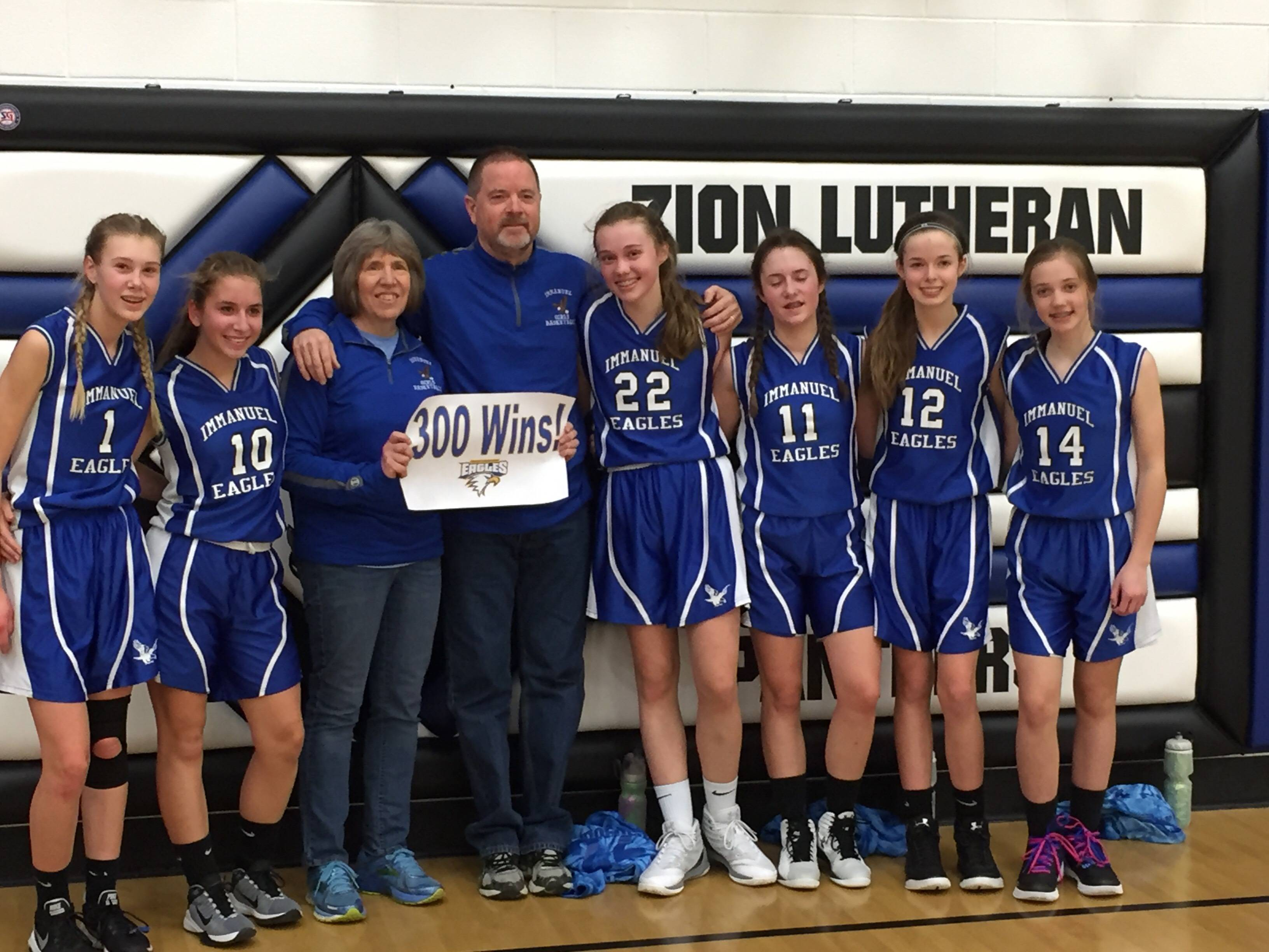 On Feb. 3, the Immanuel Eagles girls' varsity basketball team join coaches Sharon Dalpini and Steve Mudd, center, who had their 300th coaching win.