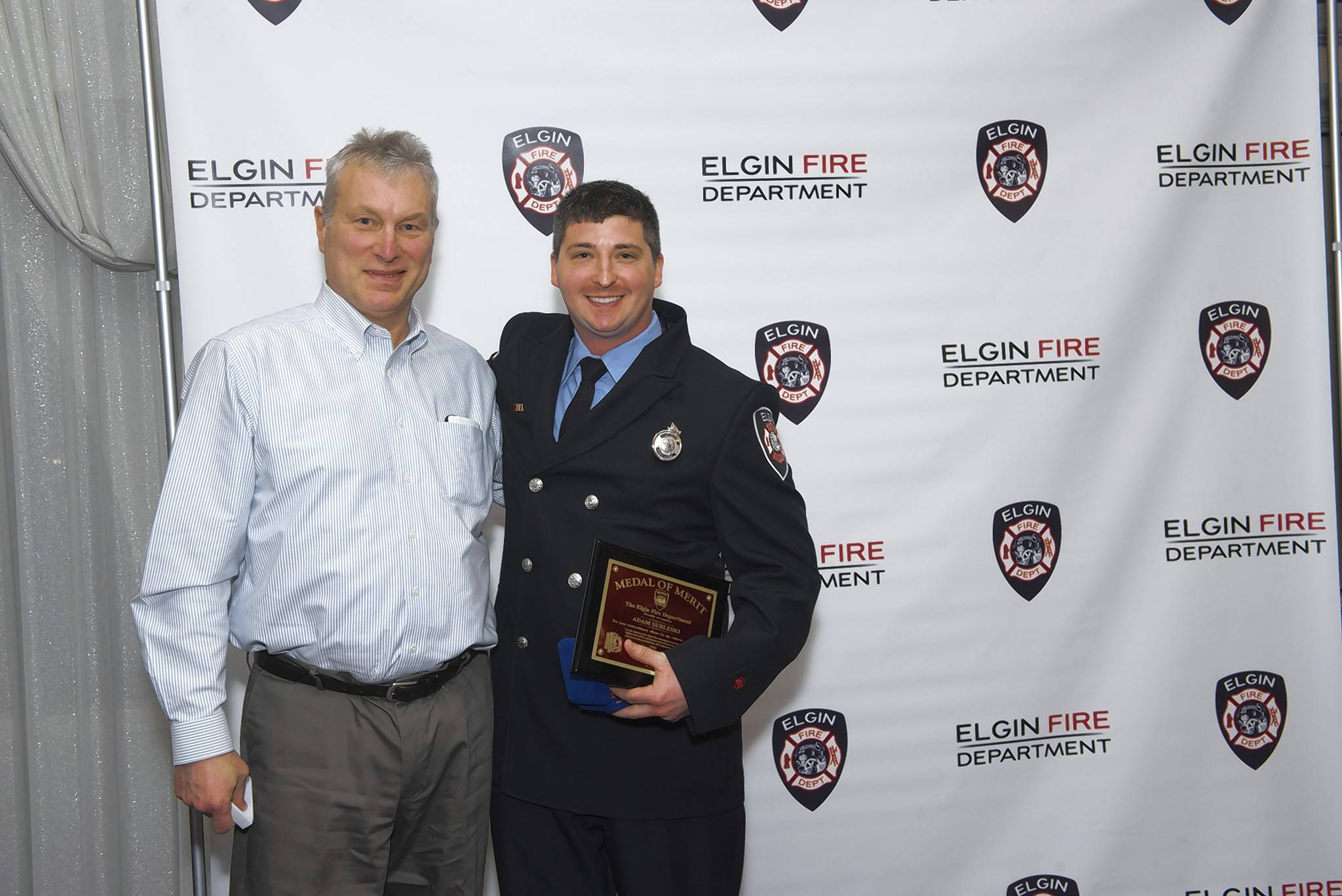 "Alan Butt, 60, of Cary, left, recently presented Elgin firefighter Alan Subleski with a fire department merit award for saving his life after his heart stopped. ""I'm extremely lucky to be alive,"" Butt said. ""Adam and the team had to move very quickly."""