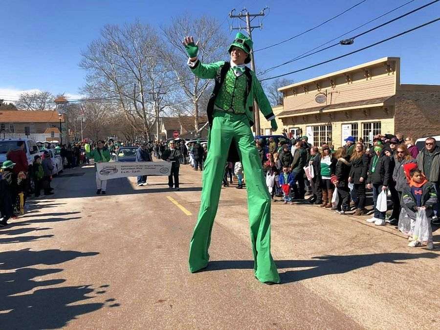 A stiltwalker waves to crowds Saturday during the Thom McNamee Memorial St. Patrick's Day Parade in East Dundee.