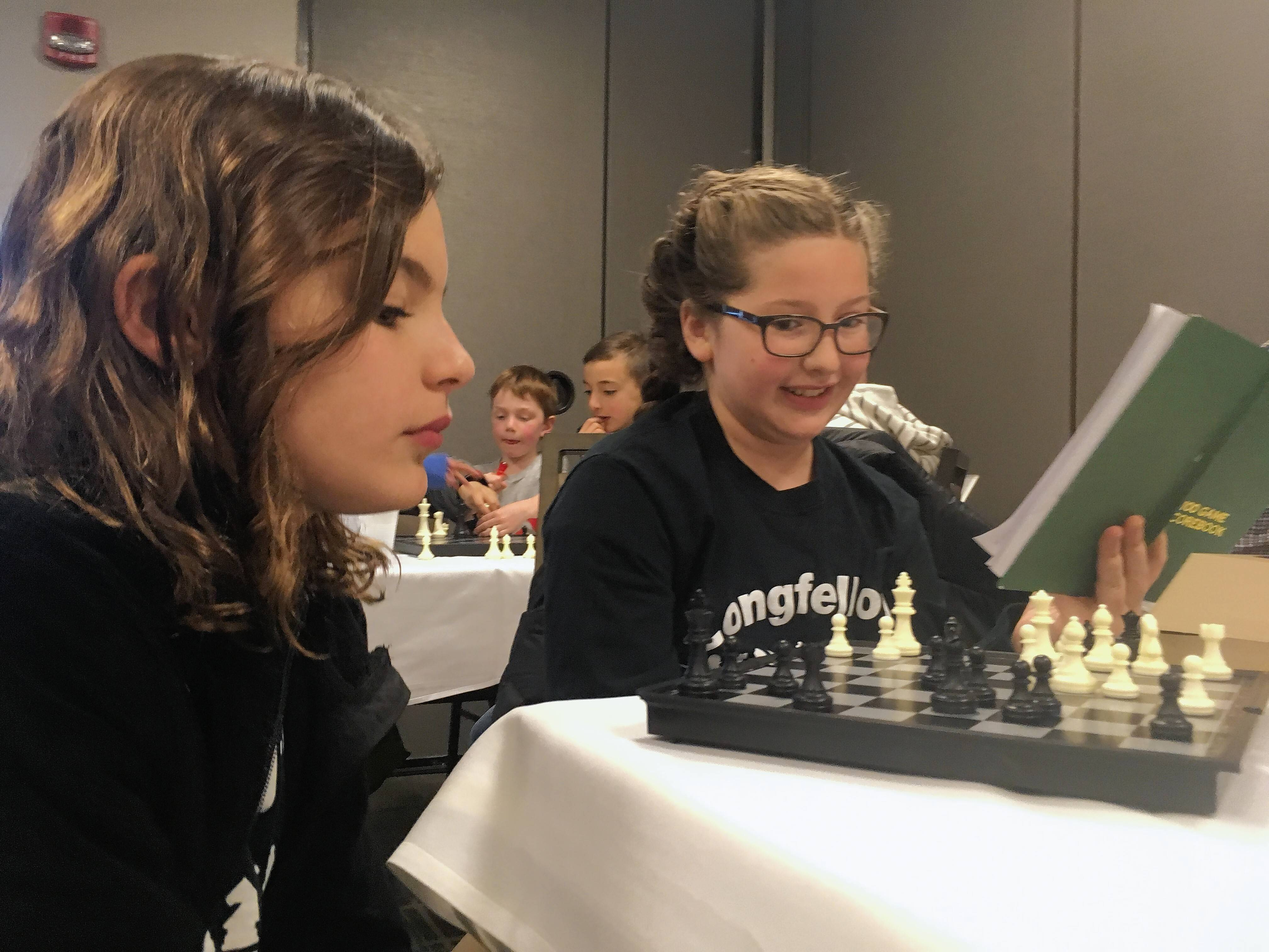 Vera Tax, 11, left, and Chloe Carlson, 10, right, from the Longfellow Chess Club in Wheaton review strategy between matches Saturday at the Illinois State Chess Championship in Schaumburg.