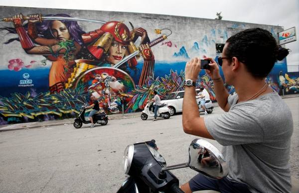 A Tourist Takes A Picture Of A Graffiti Covered Wall In The Wynwood Neighborhood Of